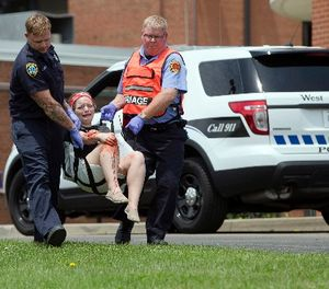 In a May 25, 2016 file photo, emergency personnel carrying a volunteer with simulated injuries is carried during a training exercise for an active shooter at Hopewell Elementary School, in West Chester, Ohio. (AP Photo/John Minchillo, File)
