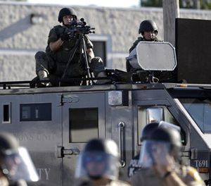 In this Aug. 9, 2014, file photo, a police tactical team moves in to disperse a group of protesters following the shooting of a young black man by a white policeman in Ferguson, Mo. (AP Photo/Jeff Roberson, File)