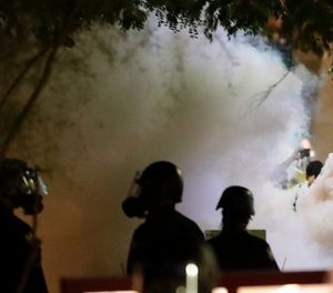 In this Aug. 22, 2017 file photo shows smoke billowing after police used tear gas on protesters outside a rally held by President Donald Trump in downtown Phoenix. (AP Photo/Matt York, File)