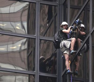 A man scales Trump Tower on Wednesday using suction cups. New York police officers dragged him through a window to safety. (AP Photo/Julie Jacobson)