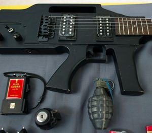 Items, prohibited on passenger airlines, and confiscated from passengers by Transportation Security Administration (TSA) officers, is displayed at Dulles International Airport in Dulles, Va., Tuesday, March 26, 2019. The items include a guitar shaped like a semi-automatic rifle, an inert grenade, and a stun gun. (AP Photo/Cliff Owen)
