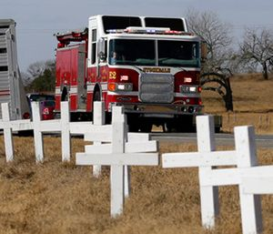 Ryland Ward, who was shot during a Nov. 5 church shooting, looks out the passenger window as he passes a memorial of crosses as he returns home after his release from the hospital in the cab of a fire truck. (AP Photo/Eric Gay)