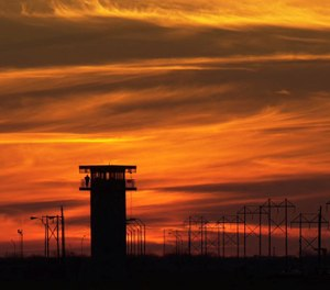 A prison guard stands on a tower at the Connally Unit near Kenedy, Texas, is seen at sunset Monday, Jan. 22, 2001. (AP Photo/Eric Gay)