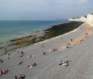 People relax on the beach at Birling Gap in Eastboune, Sussex, England. (Gareth Fuller/PA via AP)