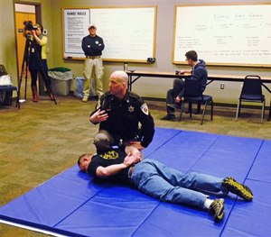 Dane County Sheriff's Deputy Eric Markgraf demonstrates the steps police are taught to take after shooting someone, during a media training session in Waunakee, Wis. (AP Image)