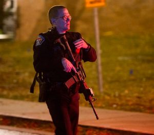 A police officer searches for a gunman near the University of Utah campus in Salt Lake City, Monday, Oct. 30, 2017. Police say a deadly shooting occurred near the school campus on Monday. (Rick Egan/The Salt Lake Tribune via AP)