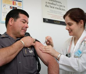 This CDC shows a law enforcement officer receiving a vaccination from a public health nurse. (CDC/James Gathany)