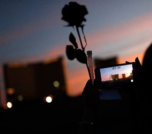 A woman takes a picture of the Mandalay Bay hotel and casino during a vigil for victims and survivors of the mass shooting in Las Vegas, Sunday, April 1, 2018, in Las Vegas. (AP Photo/John Locher)