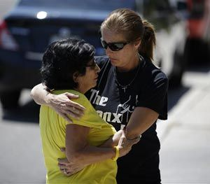 Julie Ramos, right, embraces neighbor Ana Kuhry outside of Ramos' home Wednesday, July 30, 2014, in Las Vegas. (AP Image)