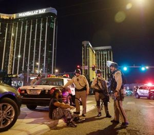 In this Sunday, Oct. 1, 2017 file photo, police officers stand at the scene of a mass shooting near the Mandalay Bay resort and casino on the Las Vegas Strip, in Las Vegas. (AP Photo/John Locher, File)