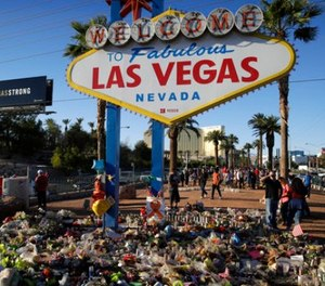 Flowers, candles and other items surround the famous Las Vegas sign at a makeshift memorial for victims of a mass shooting Monday, Oct. 9, 2017, in Las Vegas. (AP Photo/John Locher)