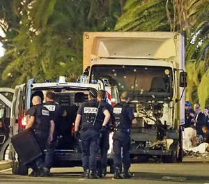 Police stand by as medical personnel attend a person on the ground, right, in the early hours of Friday, July 14, 2016, on the Promenade des Anglais in Nice, southern France, next to the lorry that had been driven into crowds of revelers late Thursday. (AP Photo)