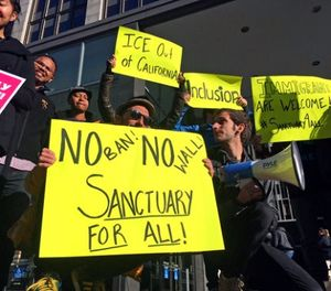 In this April 14, 2017, file photo, protesters hold up signs outside a courthouse where a federal judge was to hear arguments in the first lawsuit challenging President Donald Trump's executive order to withhold funding from communities that limit cooperation with immigration authorities in San Francisco. (AP Photo/Haven Daley, File)