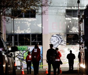 Emergency crews stand in front of the site of a warehouse fire in Oakland, Calif. (AP Photo/Marcio Jose Sanchez)