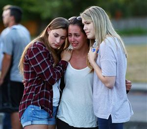 People mourn at a memorial in the parking lot of Kamiak High School Sunday, July 31, 2016. (Genna Martin/seattlepi.com via AP)