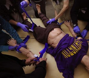 With the help of Hans the manikin, students in the Stop the Bleed program learn how to apply tourniquets at Harborview Medical Center. (Photo/Seattle Times)