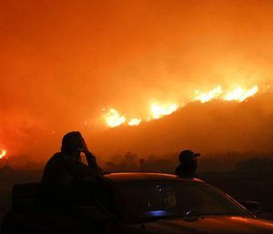 Two spectators watch as a wildfire burns along the 101 Freeway. (Photo/AP)