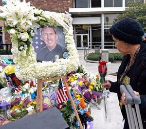 Theresa Mendoza, a formerly homeless woman who knew Whittier Police Officer Keith Boyer, adds a rose to a growing memorial for the fallen hero. (AP Photo/Nick Ut)