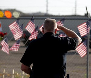 George Murphy of the Yavapi Tribal Police pays his respects at a makeshift memorial outside the Granite Mountain Interagency Hotshot Crew fire station, Tuesday, July 2, 2013, in Prescott, Ariz., honoring 19 firefighters killed battling a wildfire near Yarnell, Ariz. (AP Photo/Chris Carlson)