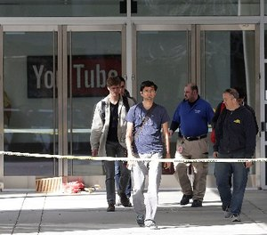 A group walks out of a YouTube office building in San Bruno, Calif., Wednesday, April 4, 2018. (AP Photo/Jeff Chiu)