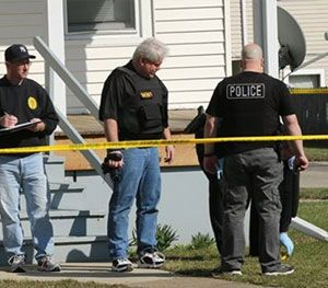 Investigators look over the scene following a police involved shooting in Zion, Ill., on Saturday. (AP Image)