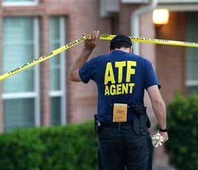 An ATF agent lifts crime scene tape outside the scene of two murders Thursday morning, Aug. 8, 2013, in DeSoto, Texas. (AP Image)