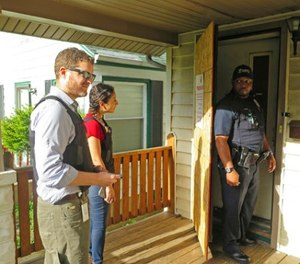 Milwaukee prosecutor Jeremy Arn, left, Safe & Sound coordinator Claudia Pizano, center, and police officer Chauncey Harris prepare to enter a vacant home on the city's north side after neighbors expressed concern about possible criminal activity. (AP Photo/Ivan Moreno)