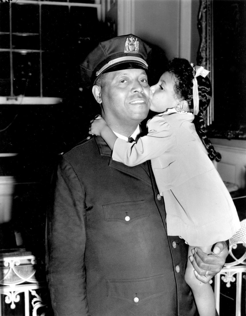 In this Sept. 4, 1941 file photo, Lt. Samuel Battle gets a kiss from his 4-year-old granddaughter, Yvonne, at City Hall in New York where he was sworn in as the first black parole commissioner in the city. (Photo/AP)