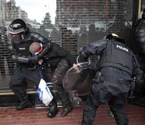 A loyalist is arrested by riot police in the center of Belfast  Northern Ireland, Friday, Aug. 9. (AP Image)