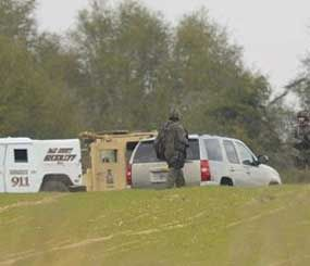 Armed law enforcement personnel station themselves near the property of Jimmy Lee Sykes, Monday, Feb. 4, 2013 in Midland City, Ala. Officials say they stormed a bunker in Alabama to rescue a 5-year-old child being held hostage there after Sykes, his abductor, was seen with a gun. (AP Image)