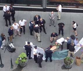 In this cell phone photo, officials examine the body of gunman Jeffrey Johnson, who was killed by police gunfire after he fatally shot Steven Ercolino, an executive at his former company, outside the Empire State Building, Friday, Aug. 24, 2012, in New York. (AP Photo/Lee Weinstein)