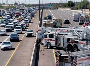 The westbound land is closed and the eastbound lane is backed up as fire and police crews work to remove the driver from a wrecked police transport, Wednesday, Sept. 23, 2015, in Mesa, Ariz. (AP Photo/Matt York)