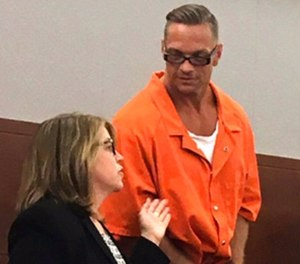In this Aug. 17, 2017, file photo, Nevada death row inmate Scott Dozier, right, confers with Lori Teicher, a federal public defender involved in his case, during an appearance in Clark County District Court in Las Vegas. (AP Photo/Ken Ritter, File)