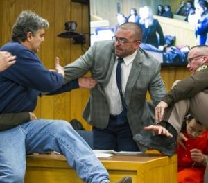 Randall Margraves, father of three victims of Larry Nassar , left, lunges at Nassar, bottom right, Friday, Feb. 2, 2018, in Eaton County Circuit Court in Charlotte, Mich.  (Cory Morse/The Grand Rapids Press via AP)
