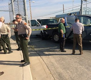 This image provided by Ray Pruitt with the Kern County Sheriffs Office shows officers looking at a pickup truck after a white prison van crashed into it at the gates of the Lerdo Pre-Trial Facility near Bakersfield, Calif., on Weds., March 2, 2016. (Ray Pruitt/Kern County Sheriffs Office via AP)