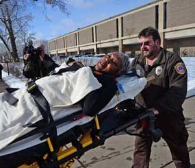 Emergency personnel brings an injured person out on a stretcher after a fight brought ambulances and police to the South High School in Minneapolis on Thursday. (AP Image)