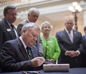 Georgia Gov. Nathan Deal signs into law a bill that will bring sweeping changes to the state's criminal justice system at the State Capitol, Wednesday, May 2, 2012, in Atlanta. (AP Photo/David Goldman)