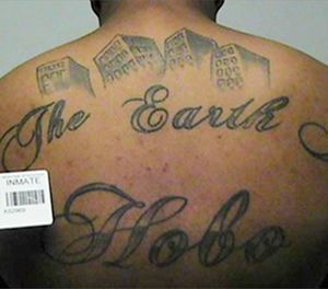 "This undated file photo in a court filing provided by the United States Attorney's office in Chicago, shows a gang member's back tattoo that reads ""The Earth Is Our Turf"", and ""Hobo."" (United States Attorney's office in Chicago via AP, File)"