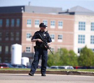 A Kane County police officer monitors the scene at Northwestern Medicine Delnor Hospital in Geneva, Ill., during a lockdown after a jail inmate being treated there managed to take a correctional officer's gun in the facility and hold an employee hostage, Saturday, May 13, 2017. (Chris Sweda/Chicago Tribune via AP)