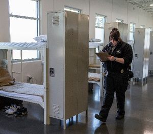 Corrections Officer Tracy Donovan writes in a clip board as she walks past rows of beds at a new facility at the Community Corrections Center in Lincoln, Neb., Thursday, Sept. 28, 2017. (AP Photo/Nati Harnik)