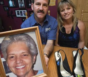 This Aug. 11, 2016 photo shows Jimmy Trout and his wife Cynthia with a photograph of Jimmy's mother, Ann Sue Metz, who was murdered in Frederick in 2009, in Frederick, Md. (AP Photo/The Frederick News-Post)