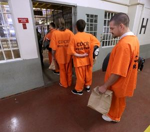 In this Thursday, Feb. 20, 2014 file photo, inmates wait to enter a there assigned cell block at the Deuel Vocational Institution in Tracy, Calif. (AP Photo/Rich Pedroncelli, File)