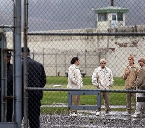 In this file photo taken Jan. 28, 2016, inmates mingle in a recreation yard in view of COs, left, at the Monroe Correctional Complex in Monroe, Wash. (AP Photo/Elaine Thompson)