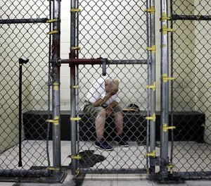 In this June 26, 2014 file photo, a U.S. veteran with post-traumatic stress sits in a segregated holding pen at the Cook County Jail after he was arrested on a narcotics charge in Chicago. (AP Photo/Charles Rex Arbogast-File)