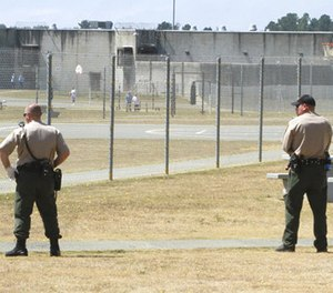 In this Aug. 17, 2011 file photo, correctional officers keep watch on inmates in the recreation yard at Pelican Bay State Prison near Crescent City, Calif. (AP Photo/Rich Pedroncelli, File)
