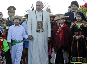 Pope Francis holds hands with children wearing traditional clothing as he walks with Bolivian President Evo Morales upon his arrival at the El Alto airport in Bolivia. (AP Photo/Gregorio Borgia)