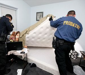 In this photo taken Friday, March 6, 2013, San Bernardino County Probation officers search a parolee room for drugs and arms during a night probation compliance sweep in Apple Valley, Calif. (AP Photo/Damian Dovarganes)