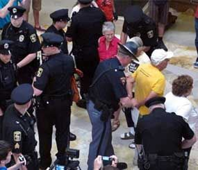 Wisconsin Capital Police arrest people gathered in the state Capitol rotunda for the daily noontime singalong on July 24 in Madison, Wis. (AP Image)