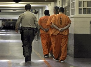 A correctional officer escorts a group of recently arrived inmates through the Deuel Vocational Institute in Tracy, Calif., in this Aug. 3, 2006, file photo. (AP Photo/Rich Pedroncelli)