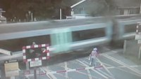 Terrifying near-miss between cyclist and train